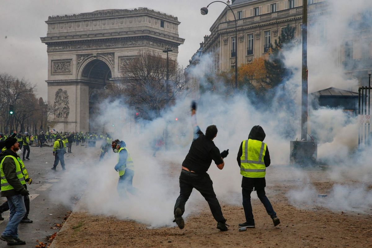 The Champs-Elysees itself was on lockdown, its glittering Christmas decorations standing in stark contrast to boarded-up storefronts and throngs of riot police manning barricades and water cannon.