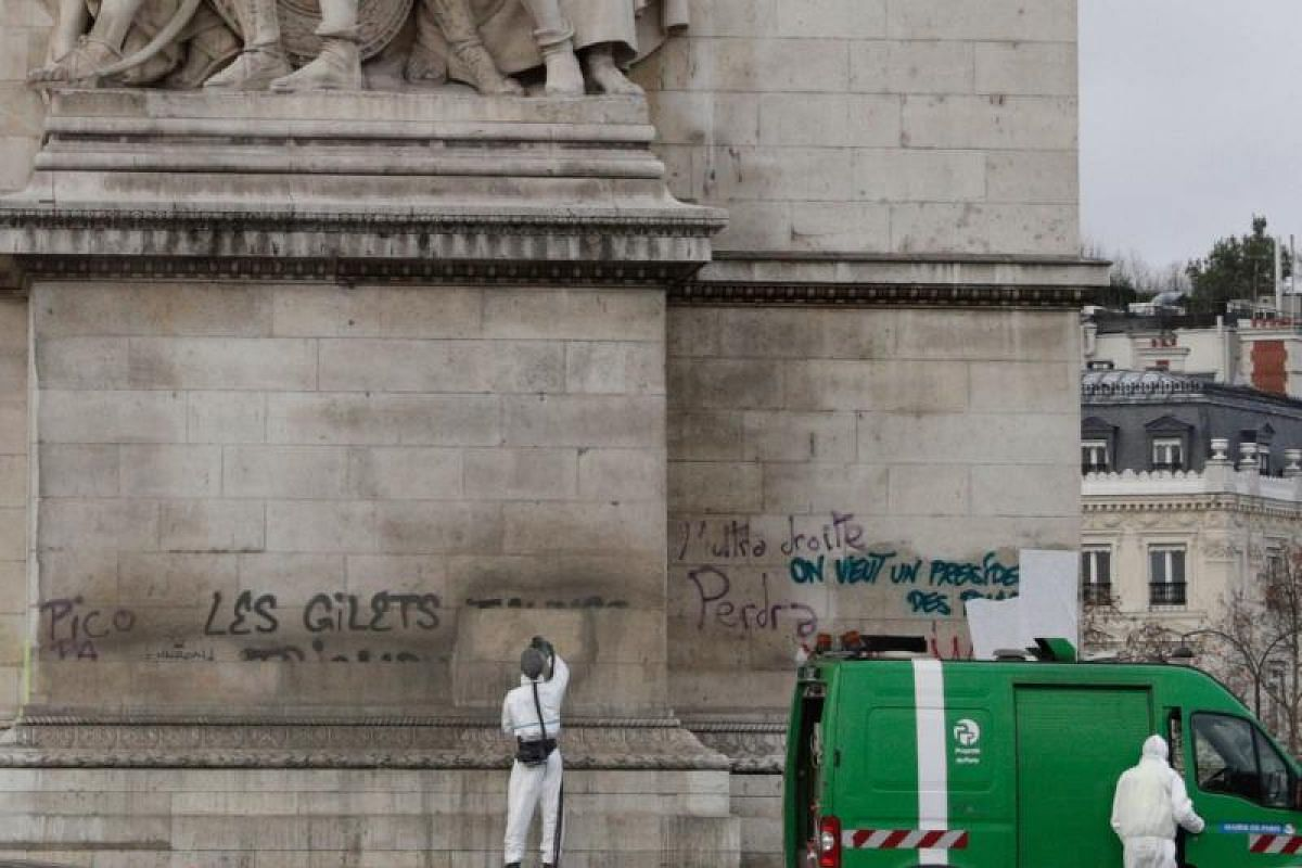 """On the facade of the towering 19th-century arch, protesters scrawled in big black letters: """"The yellow vests will triumph."""""""
