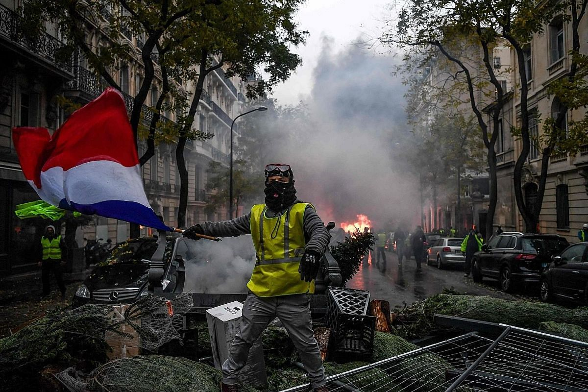 A yellow vest demonstrator holding a French flag among trampled Christmas trees during a protest against rising oil prices and living costs in Paris last Saturday. A vandalised statue of Marianne, a symbol of the French Republic and the personificati