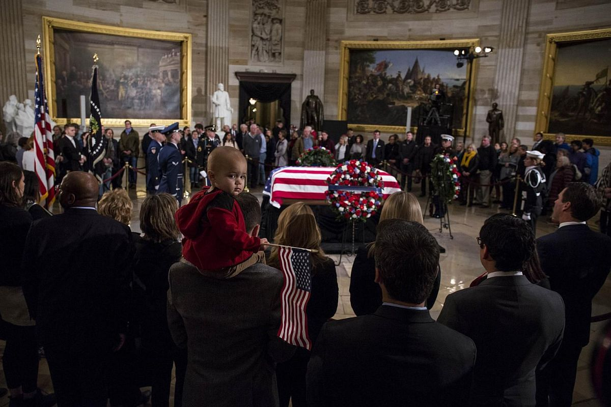 A baby holding an American flag is among those paying their respects as former US President George H. W. Bush lies in state on Dec 3, 2018 in Washington, DC.