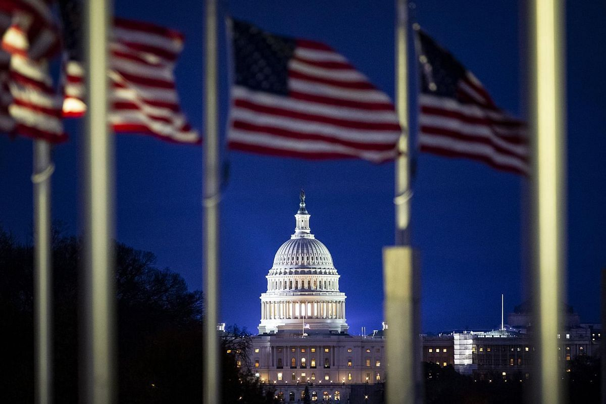 The US Capitol is seen through American flags flying at half-mast as former US president George H. W. Bush lies in state at the Capitol Rotunda in Washington, DC, on Dec 3, 2018.
