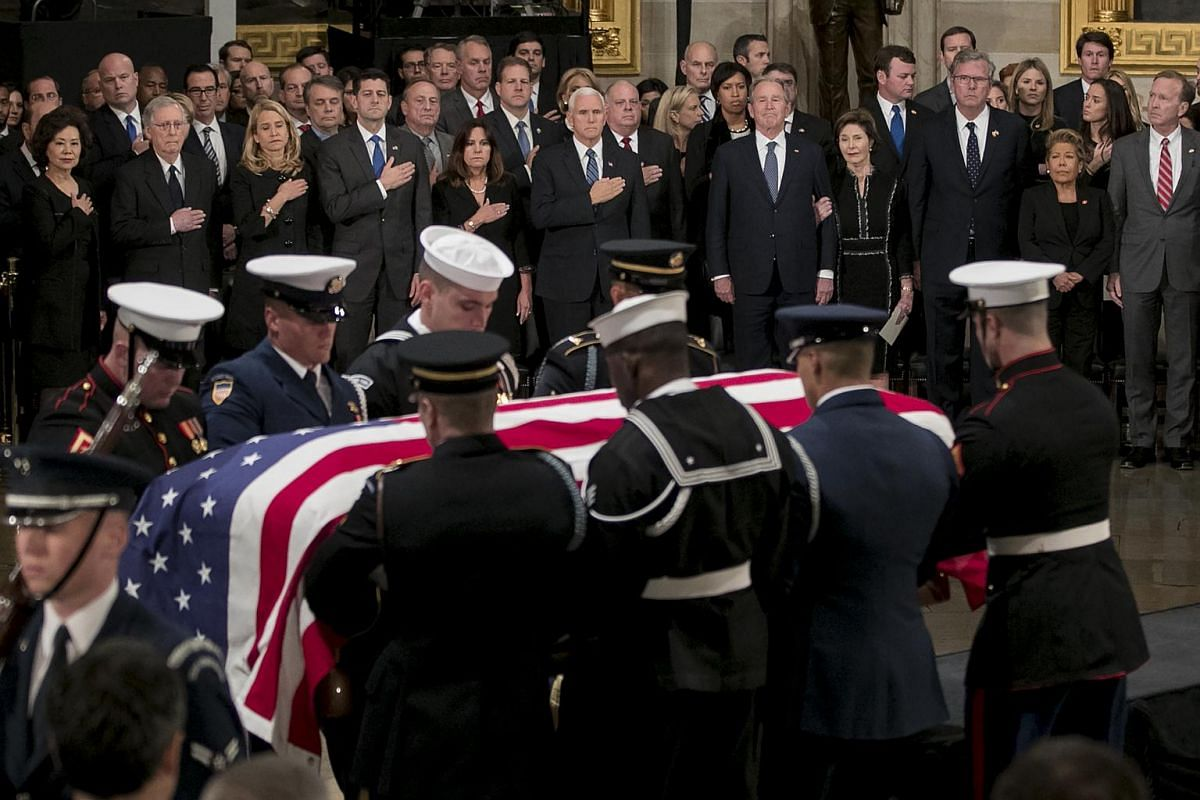 Former US president George W. Bush (fifth from right) and former First Lady Laura Bush watch as the casket of former US president George H. W. Bush arrives during a memorial service at the Capitol Rotunda in Washington, DC, on Dec 3, 2018.