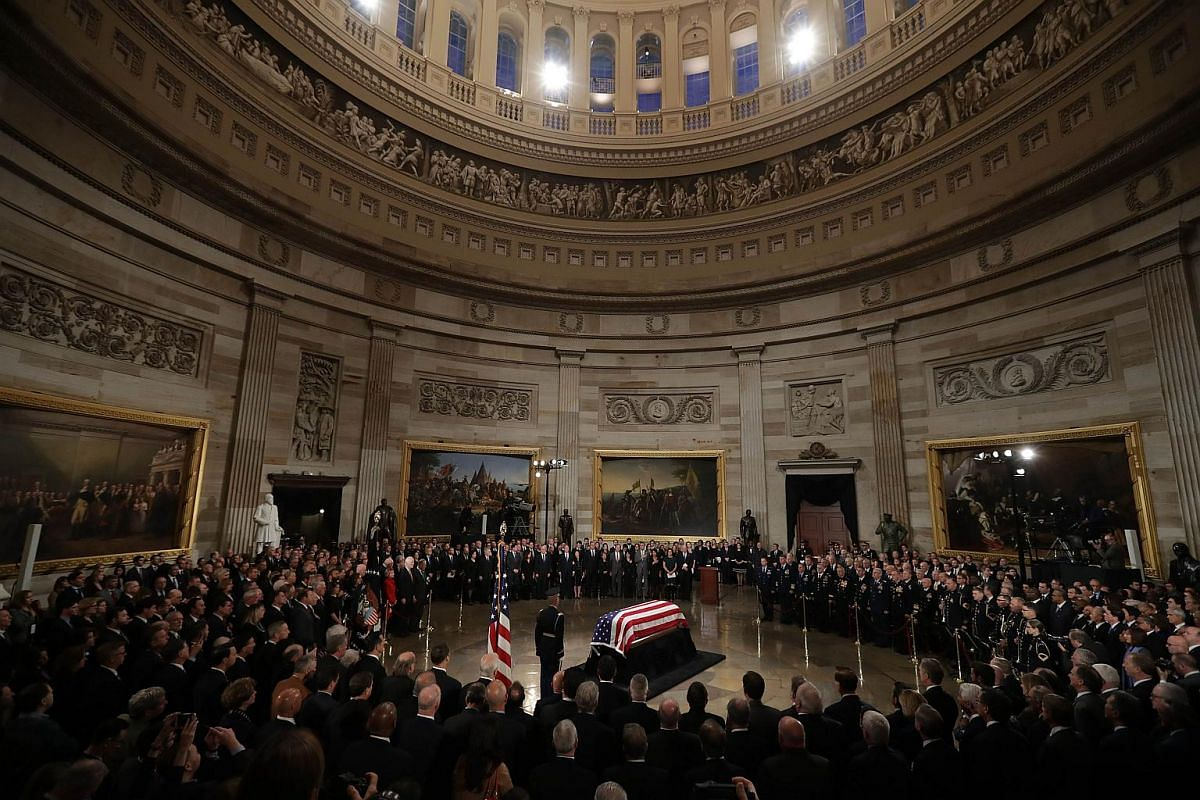 Former US president George H. W. Bush's flag-draped casket lays in state inside the US Capitol Rotunda during an arrival ceremony on Dec 03 in Washington, DC.