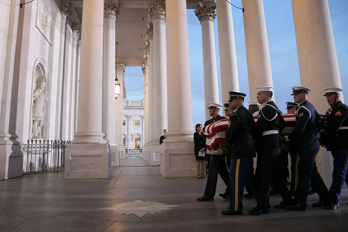 A military honour guard team carries the casket of former US president George H. W. Bush into the US Capitol in Washington, DC, on Dec 3, 2018.