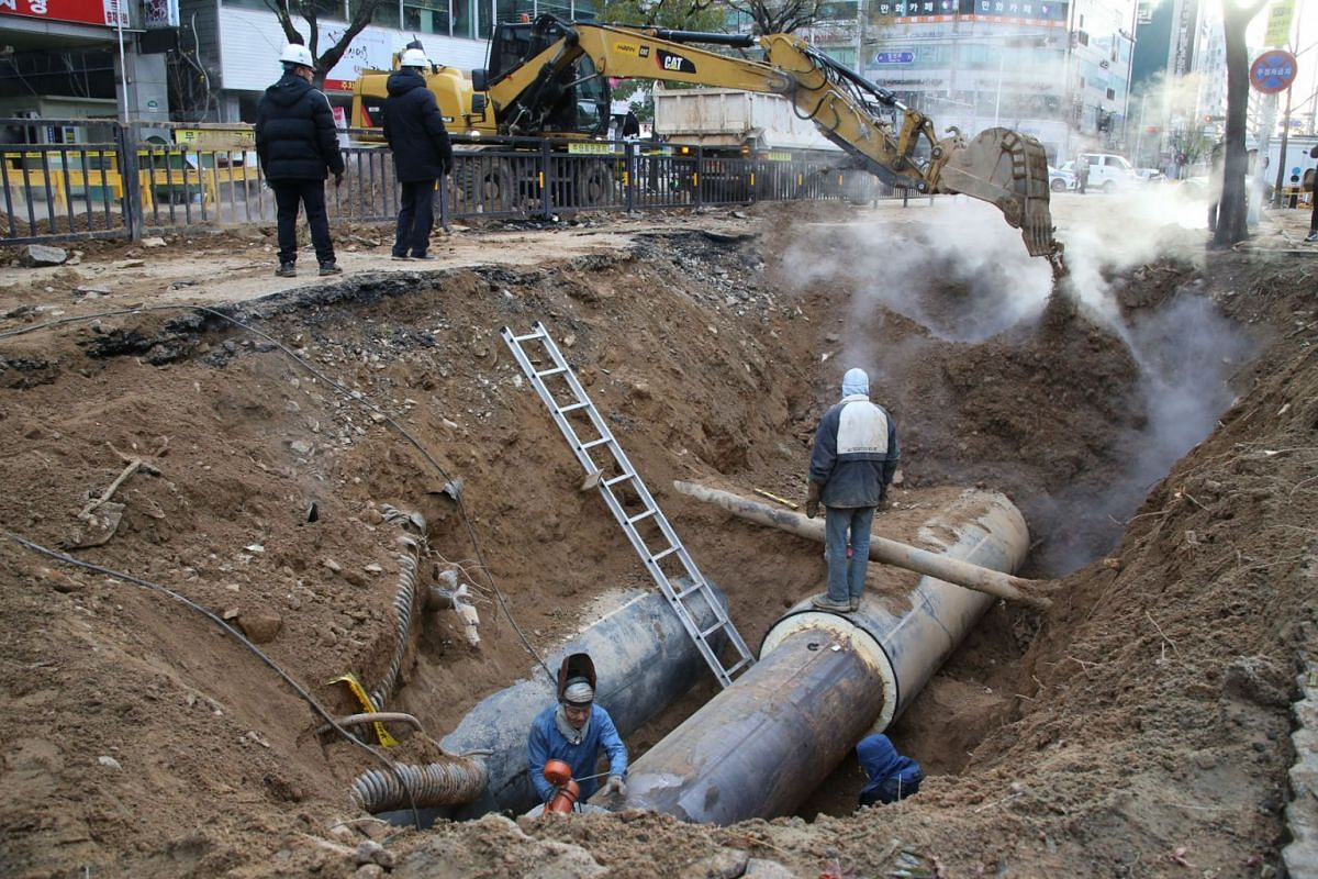 Repair work gets under way on a ruptured heating pipe under a road in Goyang, South Korea, December 4,  2018. A heating pipe burst, killing one person and injuring 20 others. PHOTO: EPA-EFE