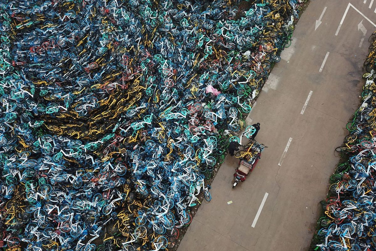 A photo released on Dec 6, 2018 shows urban management officers transporting a bicycle next to piled-up bicycles of bike-sharing services in Hefei, Anhui province, China, December 3, 2018. PHOTO: HANDOUT VIA REUTERS