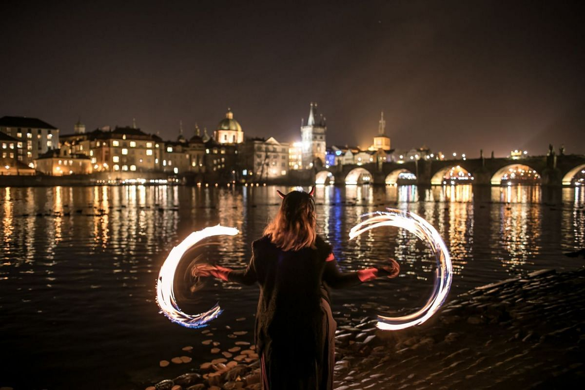 A reveler dressed as a devil waves with fire on the bank of Vltava river in Prague, Czech Republic, December 5,  2018. PHOTO: EPA-EFE