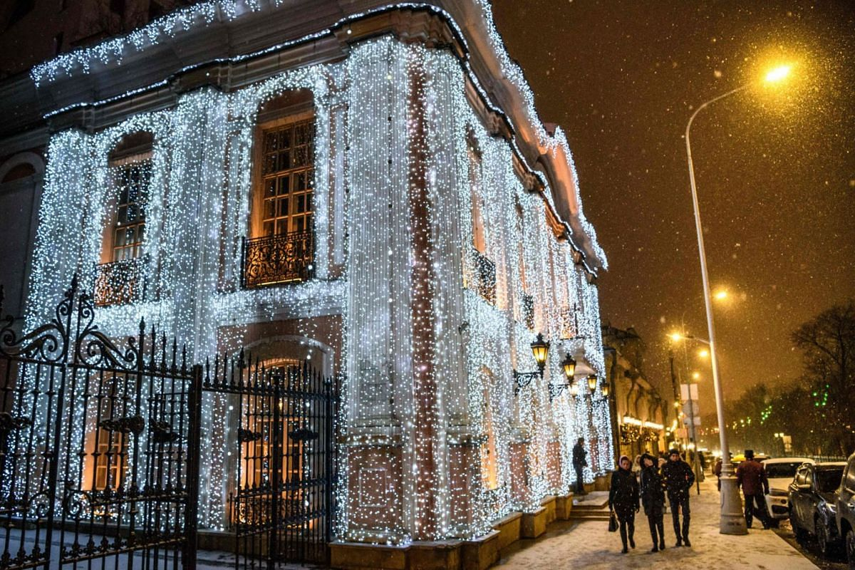 "Pedestrians walk under the snow in front of the famous restaurant ""Café Pushkin"" decorated with festive lights for the upcoming holidays in Moscow on December 5, 2018. PHOTO: AFP"