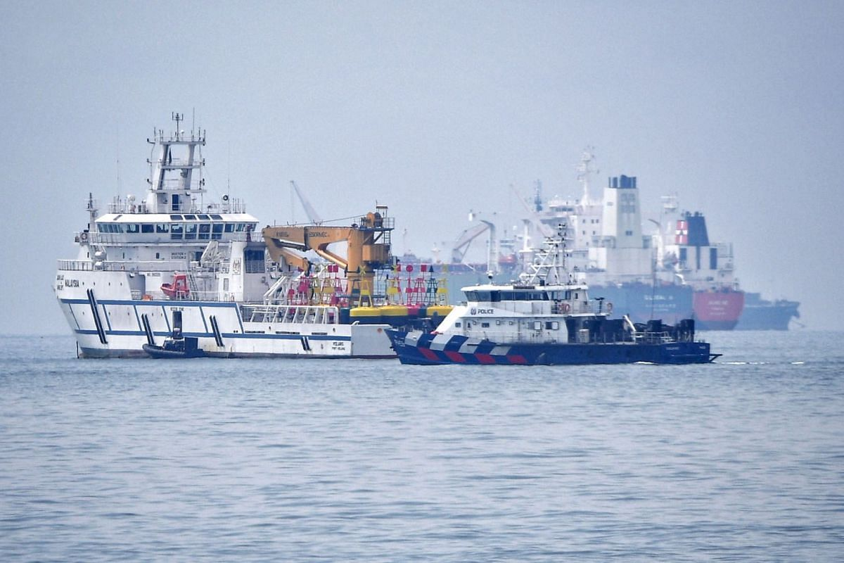 A Malaysian government vessel (left) and a Singapore Police Coast Guard vessel in Singapore territorial waters off Tuas on December 6, 2018. PHOTO: THE STRAITS TIMES/MARK CHEONG