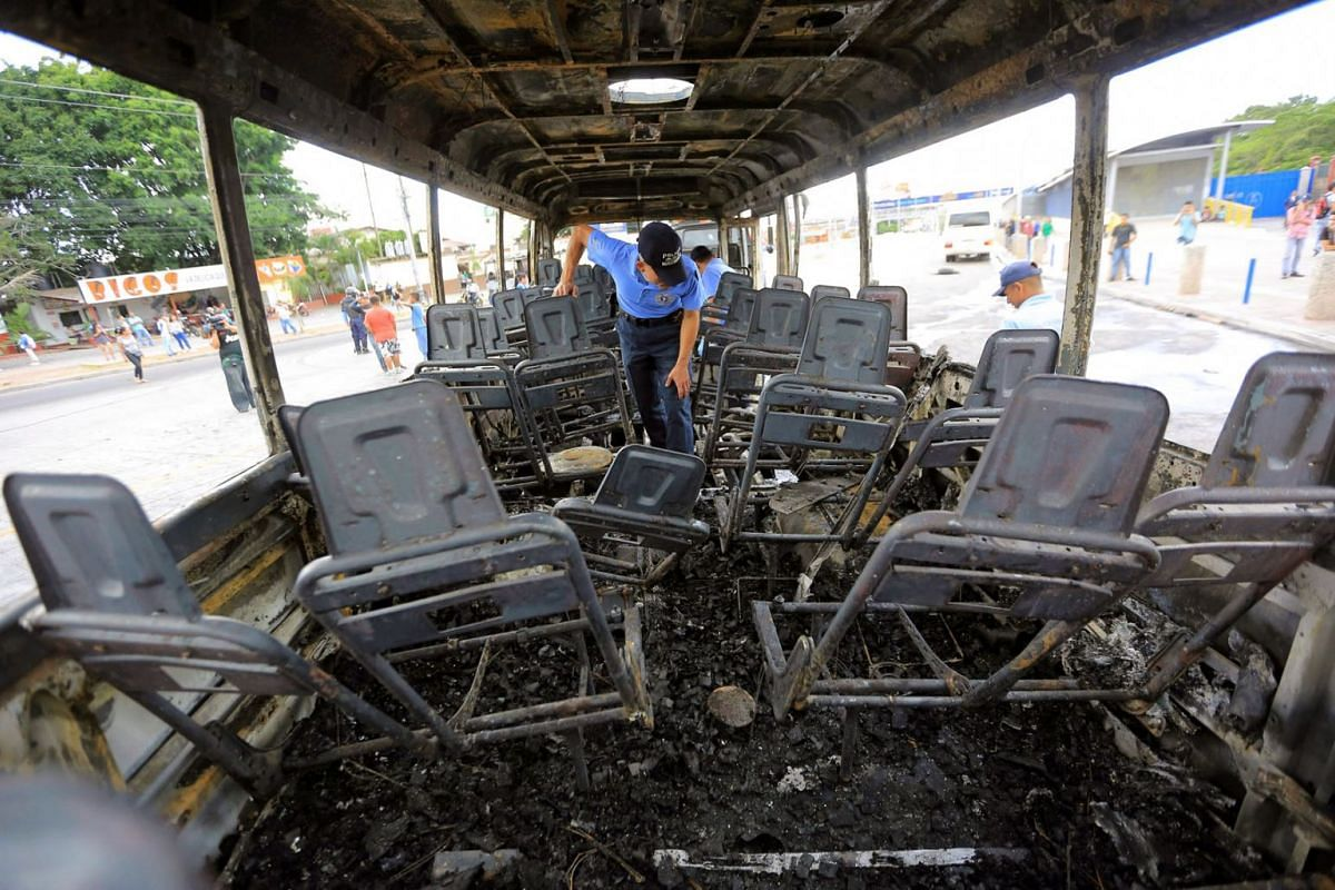 A police officer inspects a vehicle after it was set on fire in Tegucigalpa, Honduras,  December 6, 2018. According to local authorities, the perpetrators of the incident forced the passengers to get off the buses before setting them alight in protes