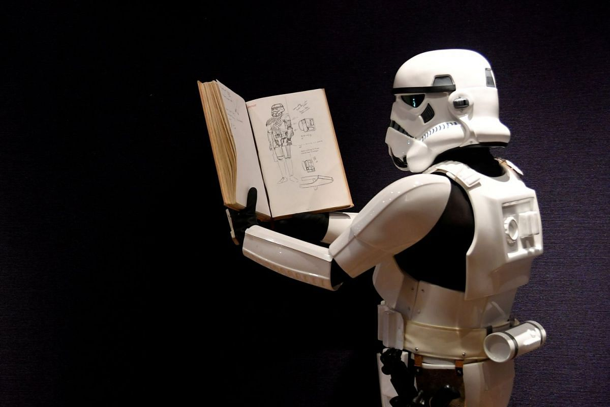 A man wearing a storm trooper costume holds a sketchbook belonging to costume designer John Mollo, and showing illustrations for Star Wars costumes, during a photo-call ahead of an auction at Bonhams in central London, Britain December 6, 2018. PHOTO