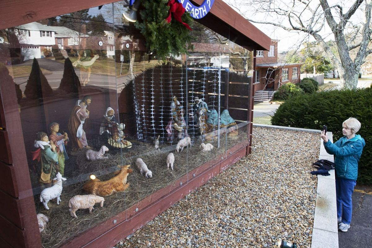 A passer-by photographs the nativity scene showing the baby Jesus in a black metal cage and the Three Wisemen behind fencing outside the St. Susanna Church, in Dedham, Massachusetts, USA, December 6, 2018. The previous year the display showed signs n