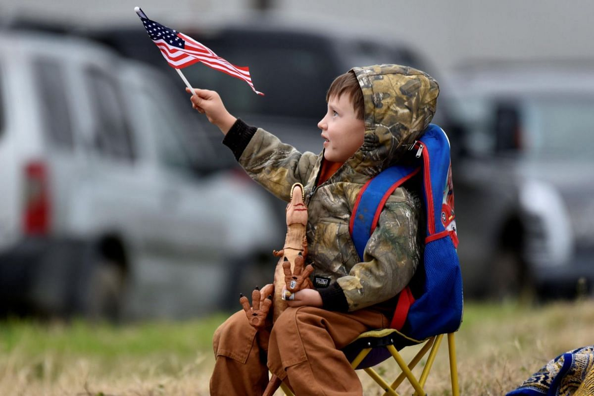 A young spectator waves an American flag along the route that the casket of former US president George H. W. Bush will travel aboard the Union Pacific funeral train in Navasota, Texas, US.