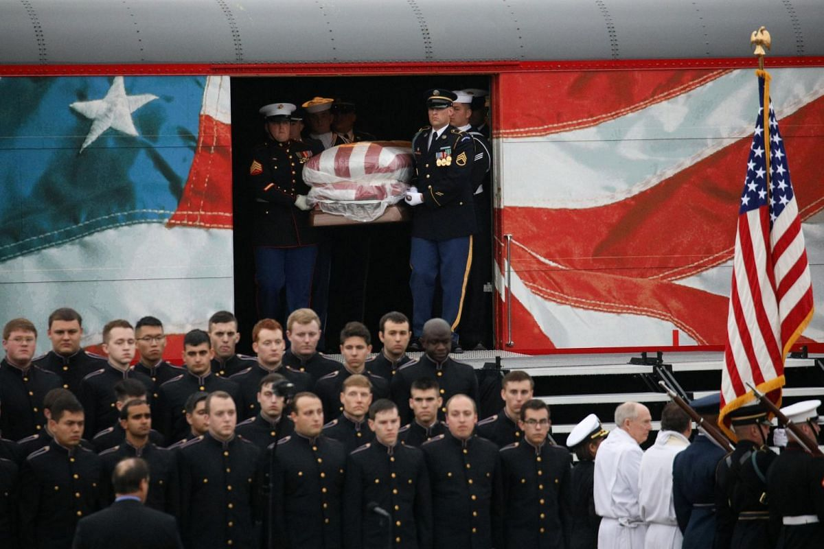 The casket of former president George H. W. Bush is carried from the Union Pacific funeral train to a hearse at Texas A&M University in College Station, Texas.