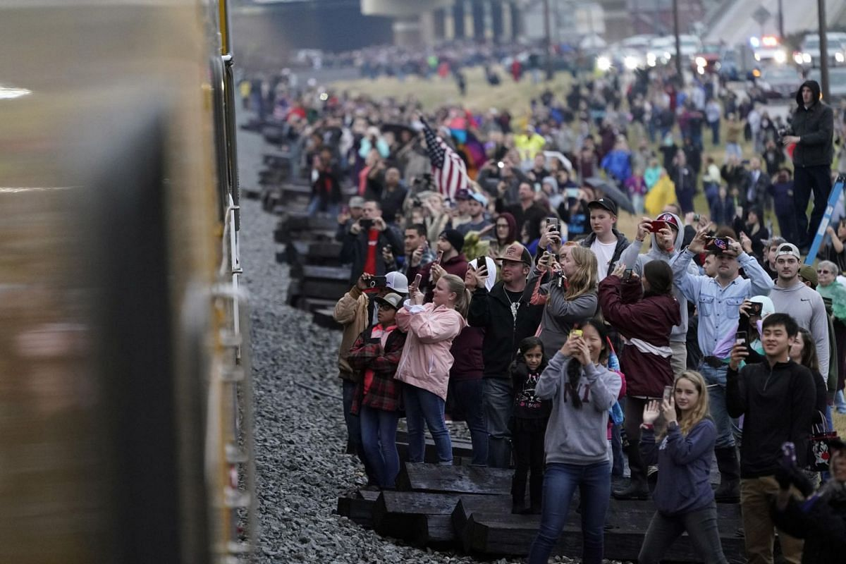 People pay their respects as the train carrying the casket of former president George H. W. Bush passes along the route from Spring to College Station, Texas, US.