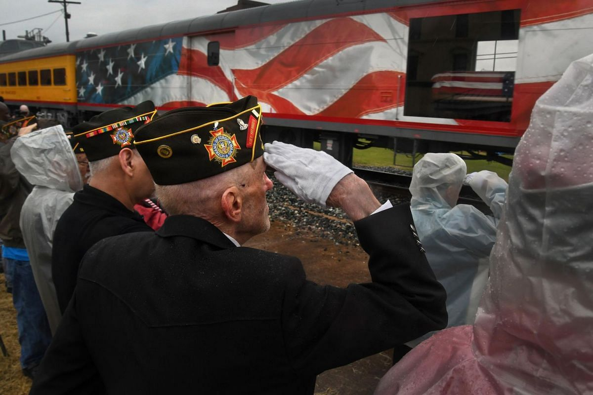 Retired Air Force Staff Sgt. Carl Dry salutes as the flag-draped casket of former president George H. W. Bush travels by train through Navasota, Texas, on its way to College Station for burial.