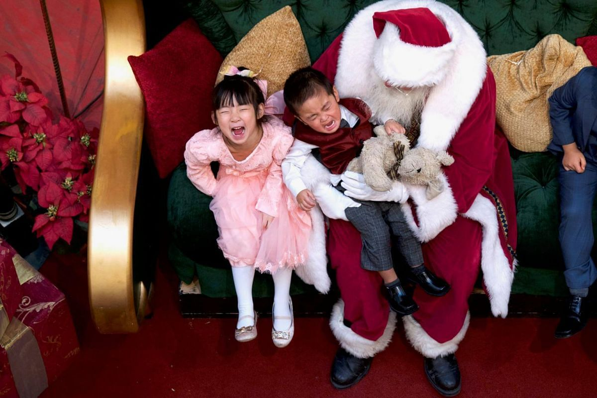 A girl laughs as her brother cries while being held by Santa Claus at the King of Prussia Mall, in Pennsylvania, on Dec 8, 2018.