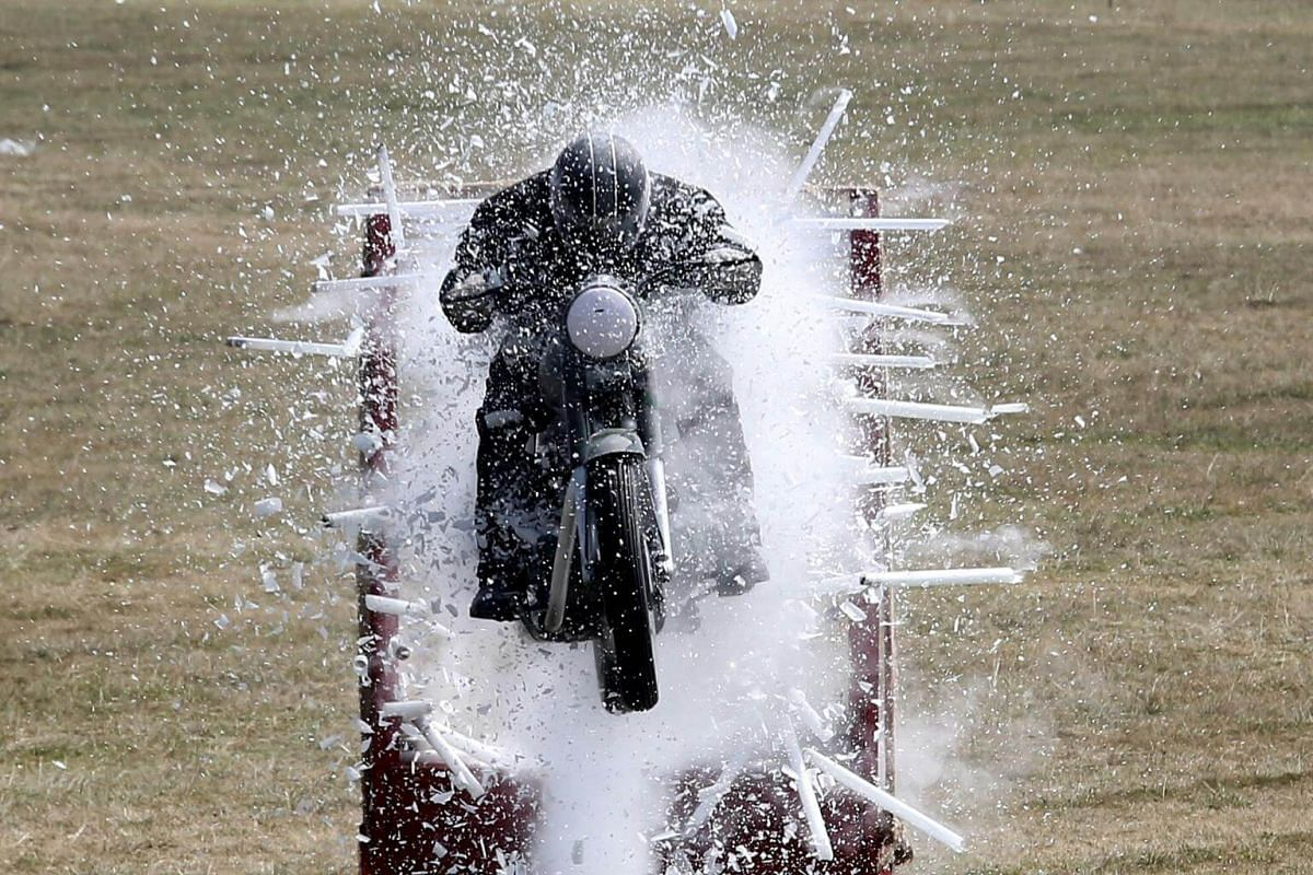 A member of the Army Service Corps motorcycle display team, known as the Tornadoes, displays his skills during the 258th anniversary of the Army Service Corps Centre and College in Bangalore, India, on Dec 9, 2018.