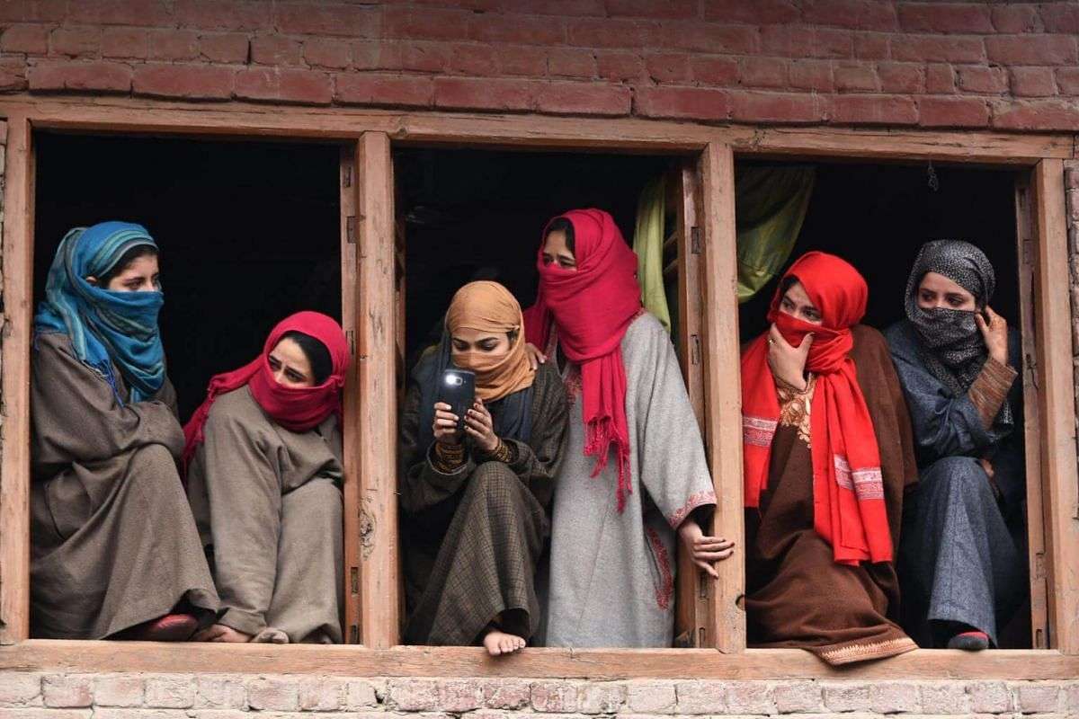 Kashmiri villagers watching a funeral procession in Hajin, north of Srinagar, on Dec 10, 2018.