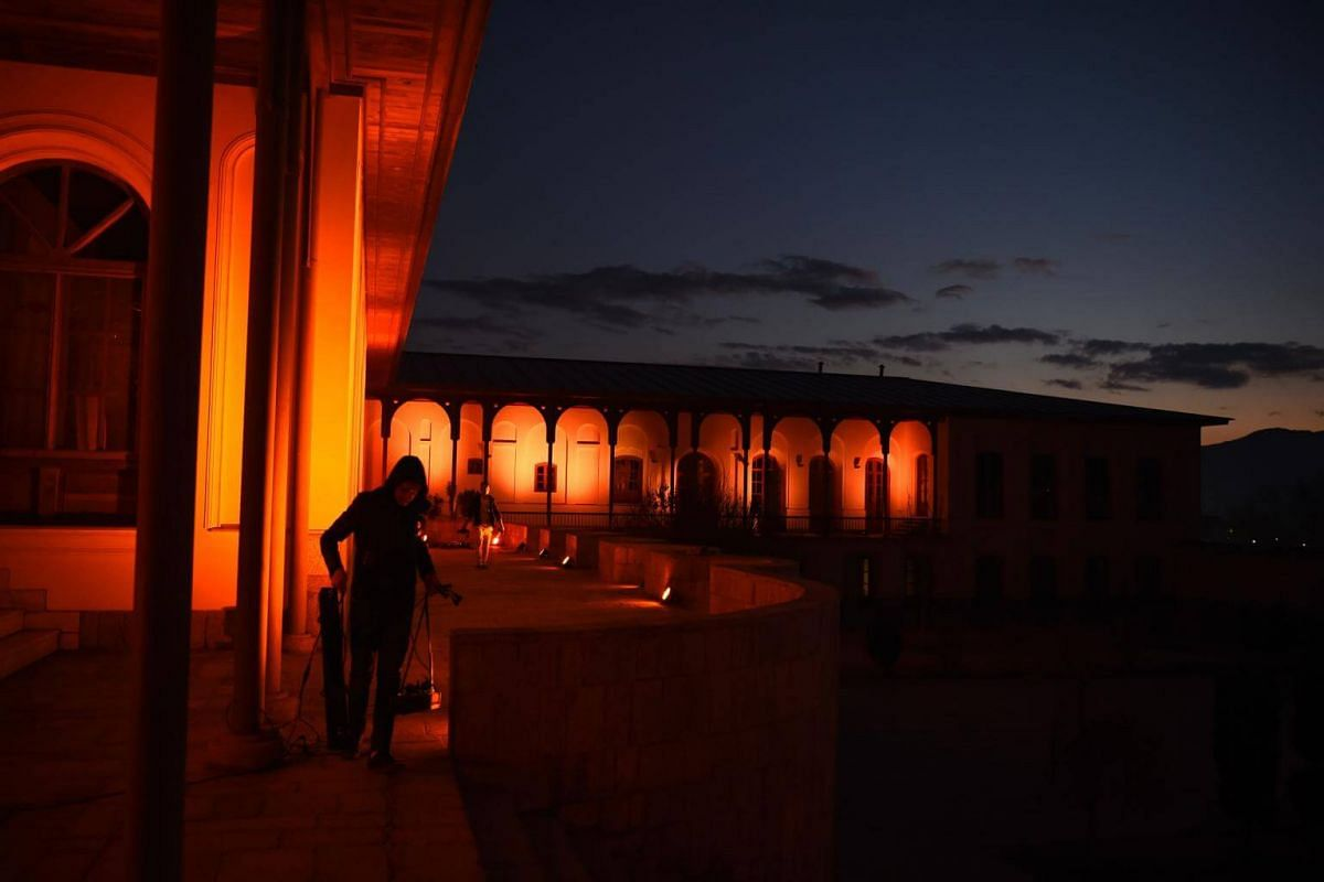 An Afghan worker at the Bagh-e-Babur Queen's Palace in Kabul on Dec 10, 2018. At dusk, the premises are lit orange as part of a United Nations women's initiative against gender-based violence.