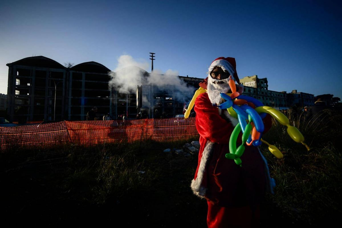 A migrant dressed as Santa Claus outside a former penicillin factory in Italy on Dec 10, 2018. Scores of migrants who lived there in hazardous conditions were being evacuated.