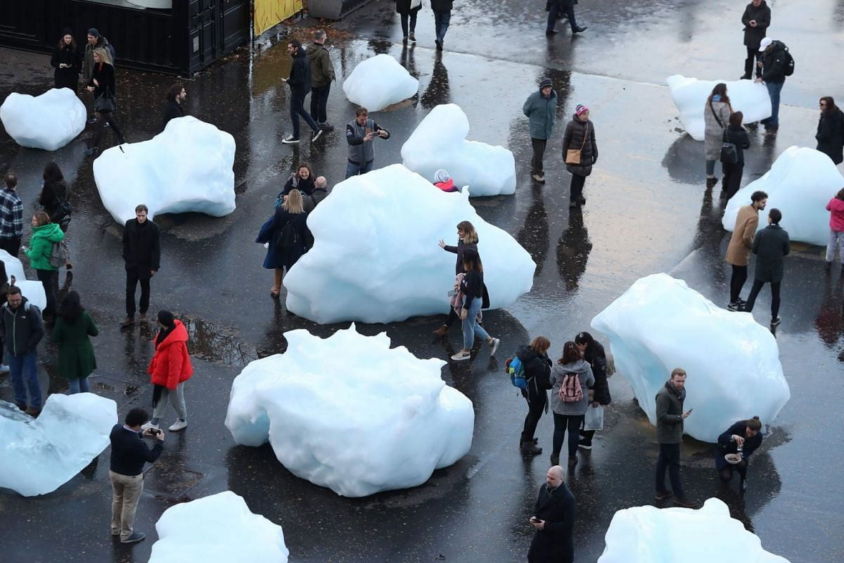 Visitors interact with blocks of melting ice, an exhibit entitled 'Ice Watch' created by Icelandic-Danish artist artist Olafur Eliasson and leading Greenlandic geologist Minik Rosing outside Tate Modern in central London on December 11, 2018. The blo