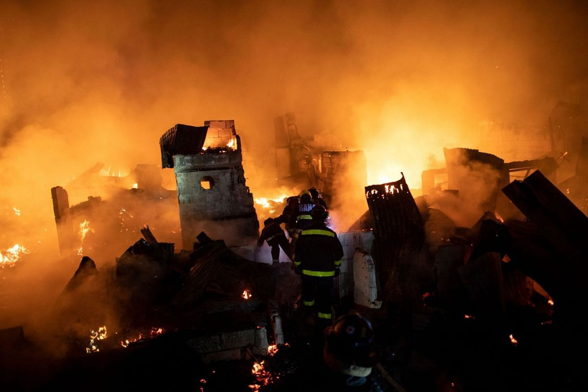 Firefighters work to extinguish a huge fire that engulfed a slum area in Manila on December 11, 2018. About 300 houses were destroyed, leaving 400 families homeless.