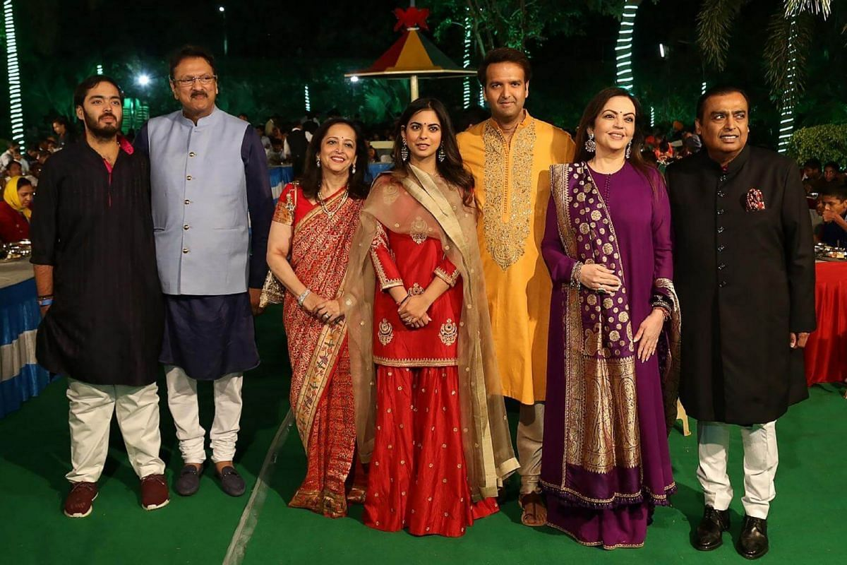 The bride and groom, Ms Isha Ambani and Mr Anand Piramal (fourth and fifth from left), posing with family members (from left) Mr Anant Ambani, Mr Ajay Piramal and his wife Swati, and Mr Mukesh Ambani and his wife Nita, during the pre-wedding ceremony