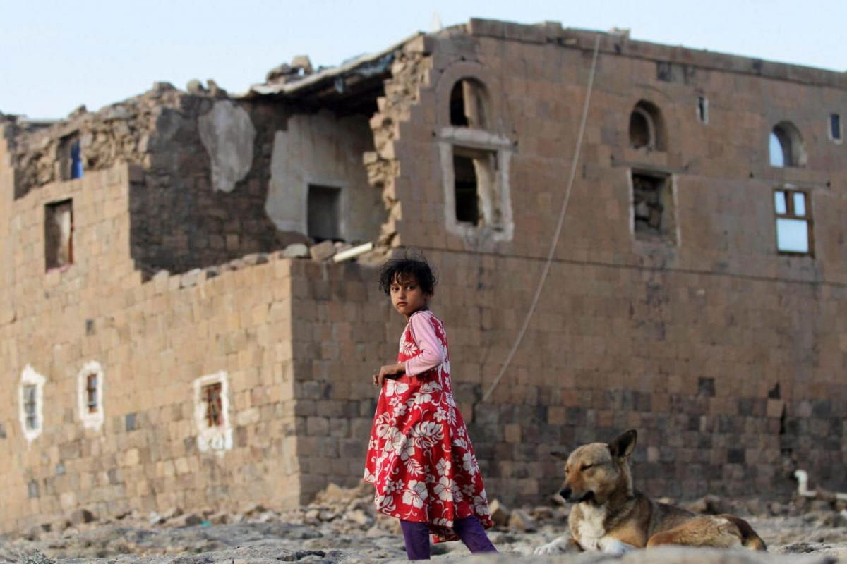 A girl walks near her house destroyed during an air strike carried out by the Saudi-led coalition in Faj Attan village, Sanaa, Yemen, on Dec 13, 2018.