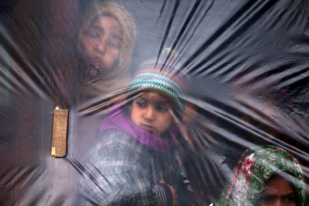 Children look out from a window on a winter's day in a village of south Kashmir's Pulwama district, on Dec 13, 2018.