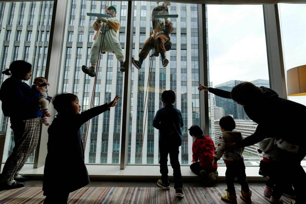 Children watch as workers clad in dog and wild boar costumes clean windows on the side of a hotel in Tokyo, Japan, on Dec 13, 2018.