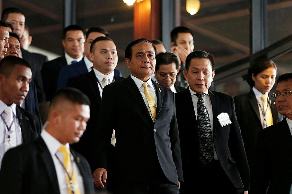 Dr Uttama Savanayana (above) says it would be ideal if Prime Minister Prayut Chan-o-cha (with yellow tie in middle picture) gets to keep his job after the Feb 24 general election. People waiting to withdraw government-allotted cash handouts recently