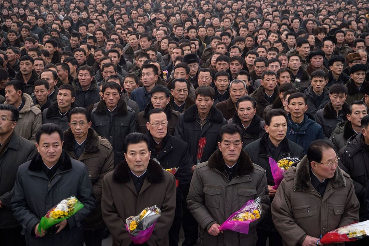 Pyongyang residents prepare to lay flowers at the statues of late North Korean leaders Kim Il Sung and Kim Jong Il during National Memorial Day on Mansu Hill in Pyongyang on December 17, 2018, marking the seventh anniversary of the death of Kim Jong