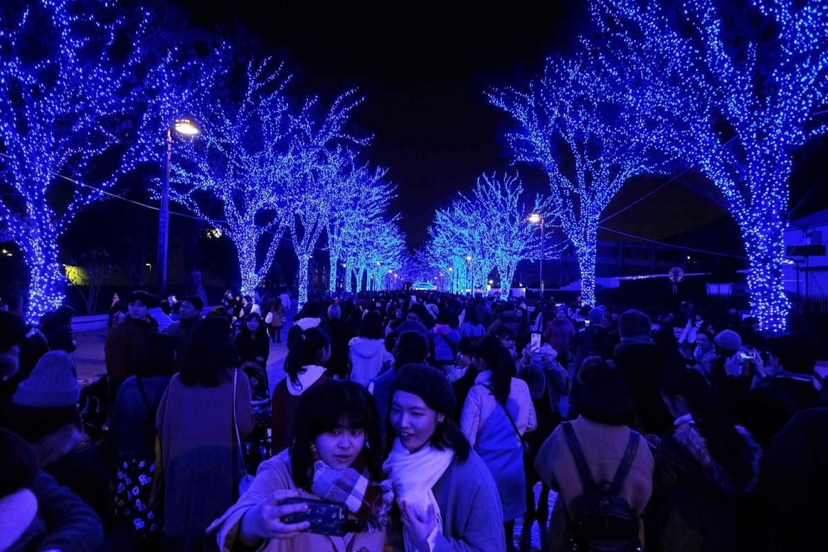People walk under winter illuminations featuring a theme of 'Blue Cave' at Yoyogi Park in Tokyo on December 16, 2018.