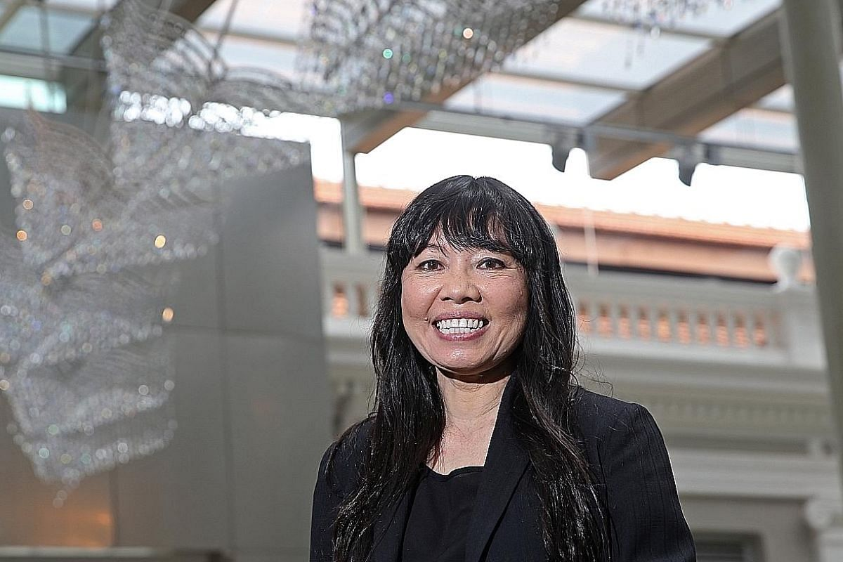 Singapore artist Suzann Victor at the National Museum Singapore with her crystal-studded sculpture, Wings Of A Rich Manoeuvre, in the background. Home-grown photographer Sean Cham's photos of migrant workers in Singapore, which are part of an exhibit