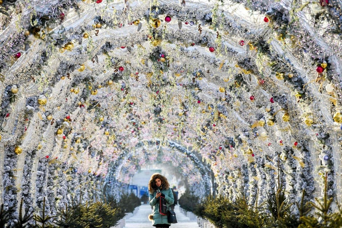 A woman walks through a tunnel decorated with festive lights for the upcoming holidays in central Moscow, on Dec 17, 2018.