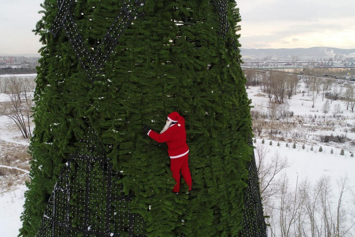 A climber, dressed as Santa Claus, decorating a 57 metre high Christmas tree in a park on Tatyshev Island, located in the middle of the Yenisei River in the Siberian city of Krasnoyarsk, Russia, on Dec 17, 2018.