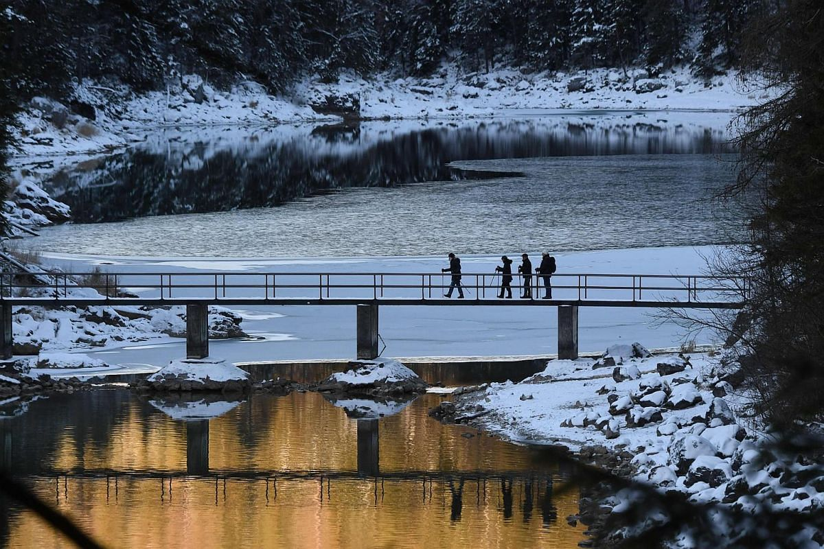 Strollers walk over a bridge of the Eibsee lake near the Bavarian village of Garmisch-Partenkirchen, southern Germany, during sunny winter weather with temperatures of minus three degrees on Dec 18, 2018.