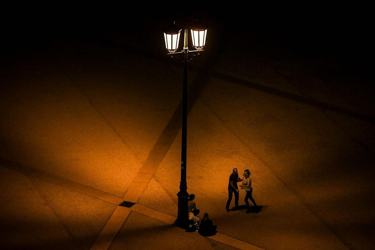 A couple dances under the light of a lamppost at Comercio square in Lisbon on Dec 17, 2018.