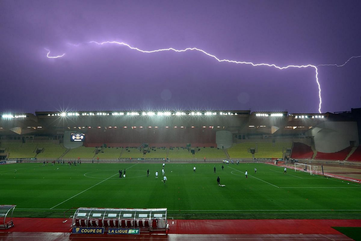 Lightning races across the sky above the Louis II Stadium as players warm up before a French League Cup football match between Monaco and Lorient, in Monaco, on Dec 19, 2018.