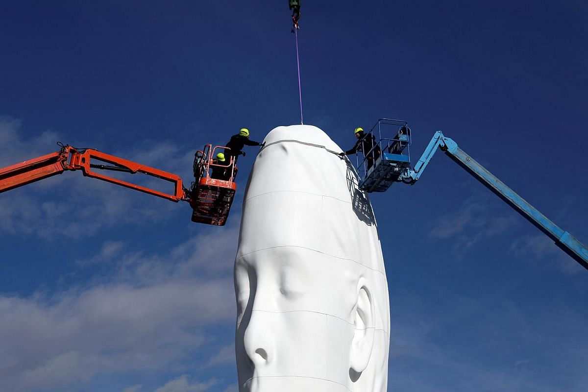 """Workers put the finishing touches on a statue entitled """"Julia"""" by Spanish artist Jaume Plensa at Plaza Colon Square in Madrid, Spain, on Dec 19, 2018."""