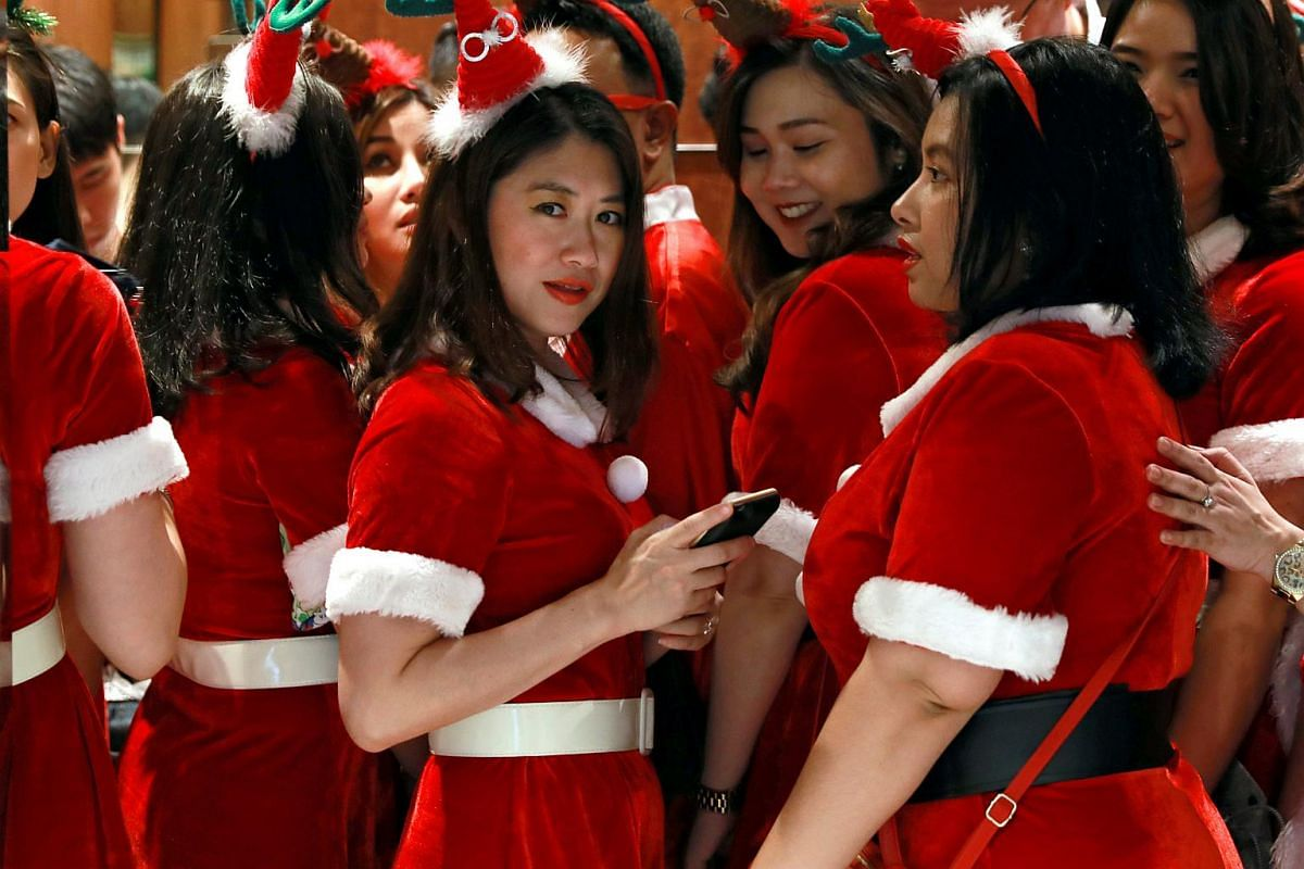 Women in Santa outfits are seen in a lift at an office tower in Bangkok, Thailand, on Dec 19, 2018.