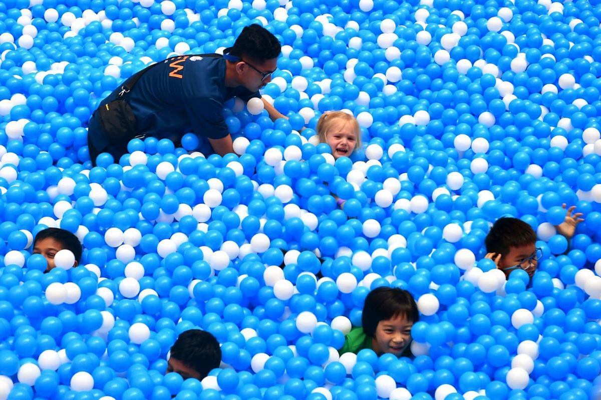 """A ball pit """"lifeguard"""" attending to a child at the suspended ball pit at City Square Mall on Feb 4, 2018. The ball pit is part of City Square Mall's three-storey Airzone, which has been touted as the world's first net playground built in a shoppi"""
