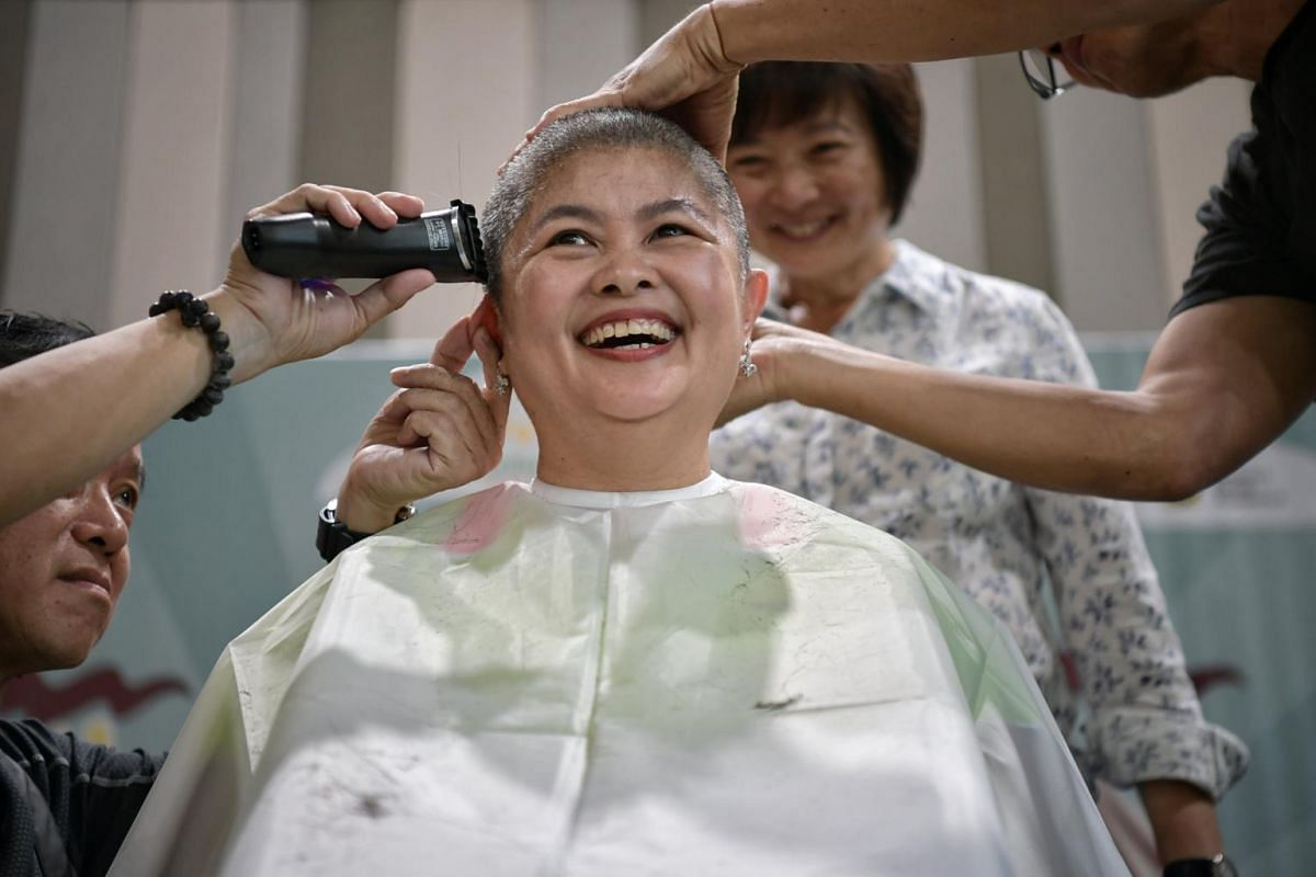 Mrs Josephine Low, corporate operational director of Sunflower Childcare Group, having her head shaved, as Nee Soon GRC MP Lee Bee Wah looks on, in a show of support for young cancer patients on June 22, 2018. The Children's Cancer Foundation's s