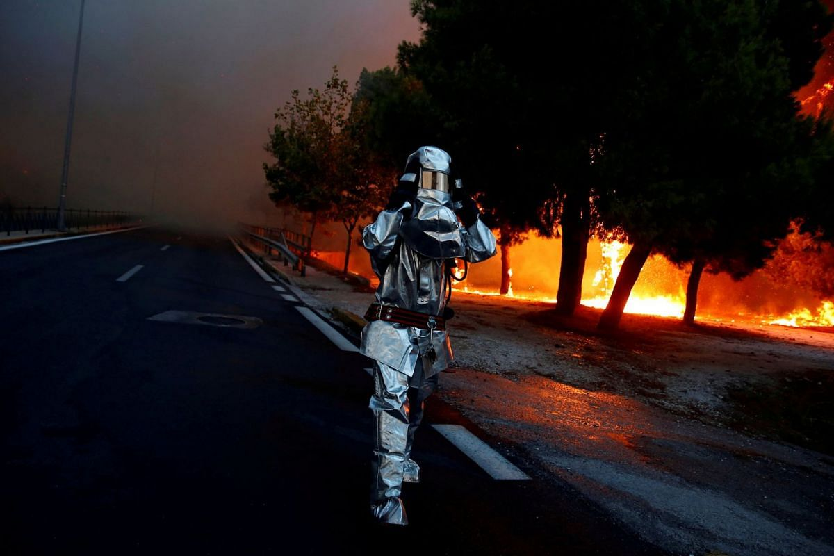 A firefighter dons a flame resistant uniform as wildfire burns in the town of Rafina, near Athens, Greece, on July 23, 2018. Rafina faced one of the largest wildfires in the deadliest fire season to hit Greece in more than a decade.