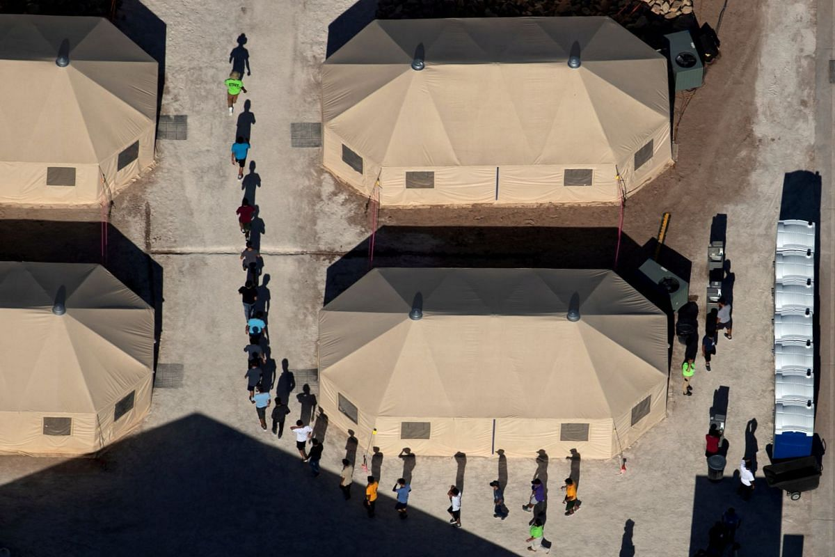 Immigrant children, suspected of illegal border crossings, are led in single file between tents by staff at a detention facility next to the Mexican border in Tornillo, Texas, on June 18, 2018.