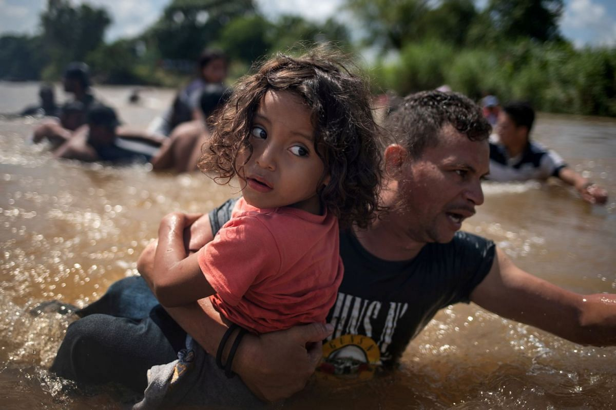 Luis Acosta holds five-year-old Angel Jesus as they cross the Suchiate River into Mexico from Guatemala in Ciudad Hidalgo, Mexico, on Oct 29, 2018. The pair from Honduras are part of a caravan of migrants from Central America en route to the United S