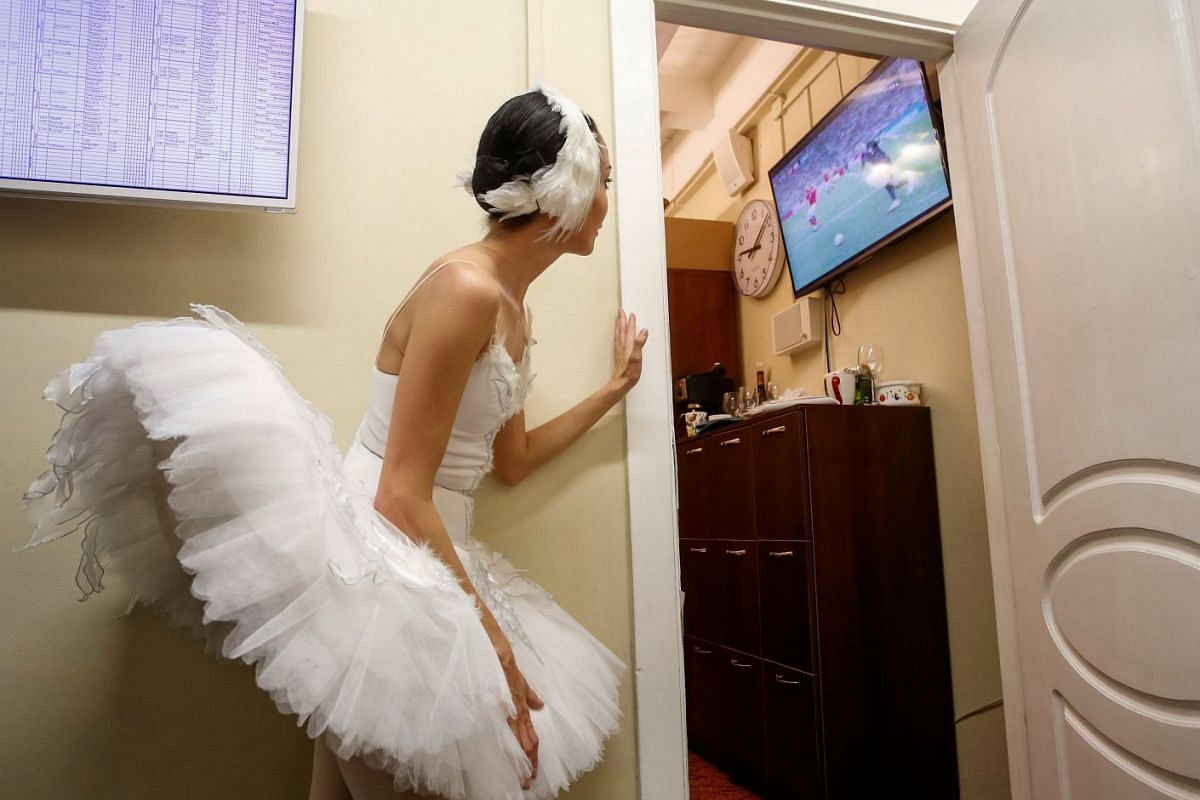 A ballerina watches the broadcast of the World Cup quarter-final match between Russia and Croatia, at the Mikhailovsky Theatre, in St Petersburg, Russia, on July 7, 2018.