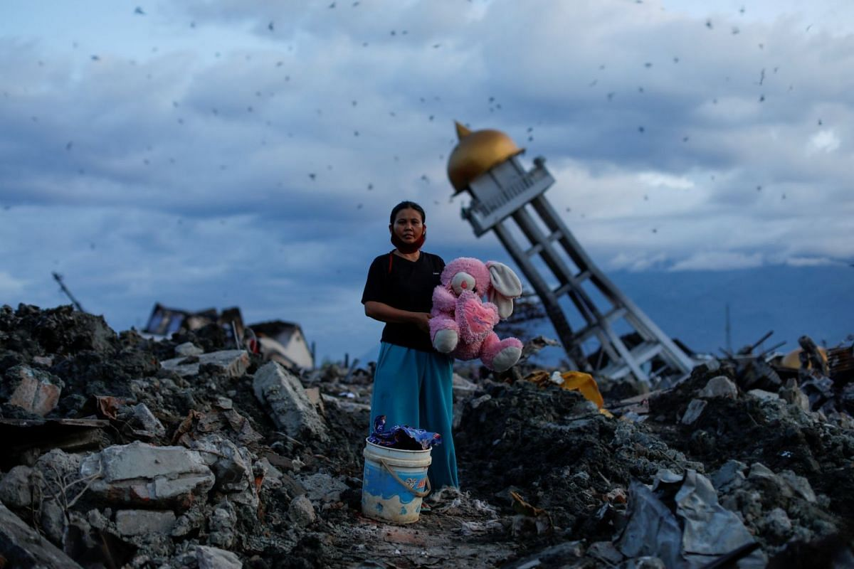 A woman holds a stuffed rabbit toy at her destroyed home where she said she lost her three children after the area was hit by an earthquake, in Palu, Central Sulawesi, Indonesia, on Oct 7, 2018.