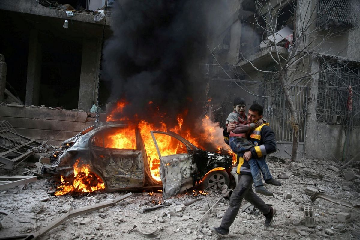 A Syria Civil Defence member carries a wounded child in the besieged town of Hamoria, Eastern Ghouta, in Damascus, Syria, on Jan 6, 2018.